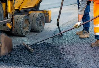Worker regulate tracked paver laying asphalt heated to temperatu - ©peuceta - stock.adobe.com